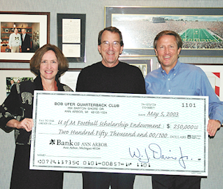 Pam Ufer Wood and Tom Ufer present Lloyd Carr with a $250,000 endowment check for athletic scholarships to the University of Michigan.