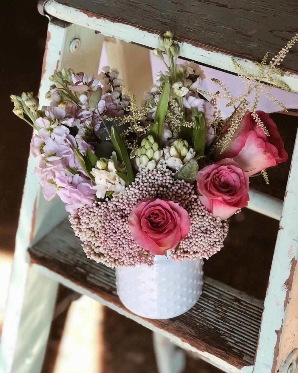 milk vase spring arrangement with astilbe rice flower and hyacinths