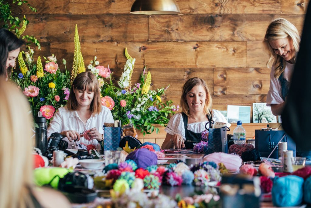 Fran and Alexia getting creative in the pompom headdress making workshop by Ollie Quinn.