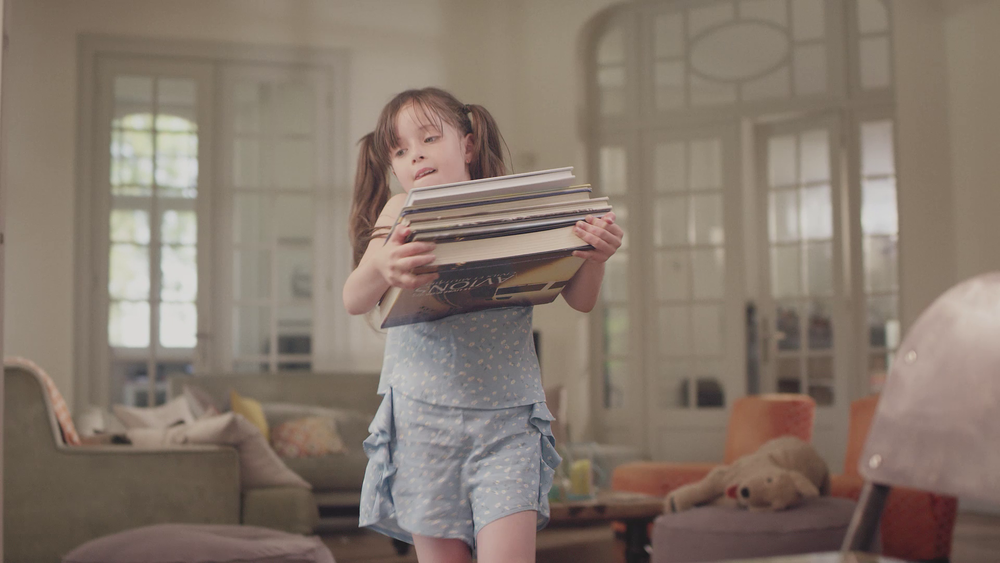 Little girl moving a pile of books