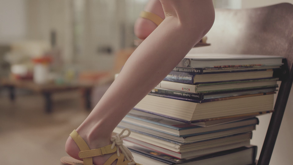 pile of books next to the legs of a little girl