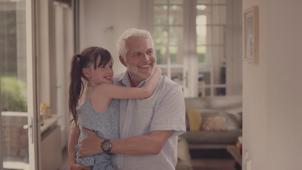 A grandfather holds his baby girl in his arms