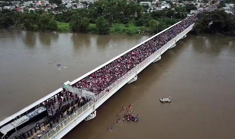 A section of the migrant caravan crosses the Suchiate River near the border between Mexico and Guatemala, via flickr.