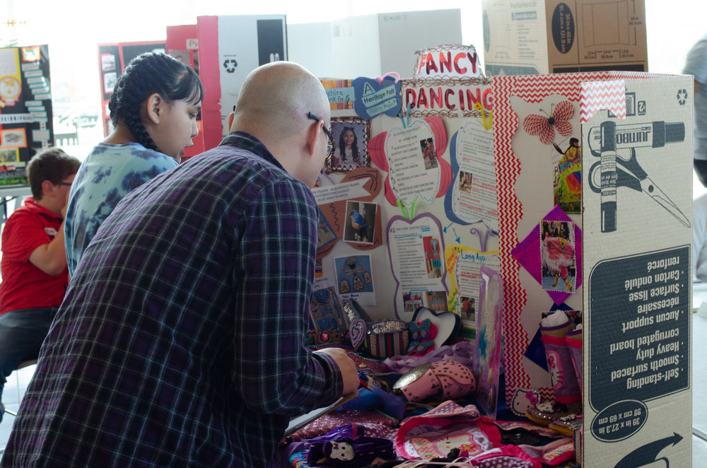 An adult examines a student's Heritage Fair project on the history and culture of Fancy Dancing.