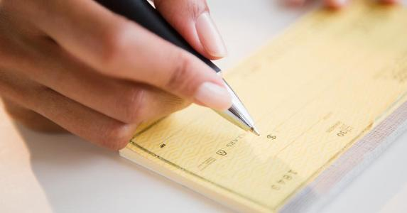 woman-writing-amount-on-yellow-check-getty_573x300.jpg