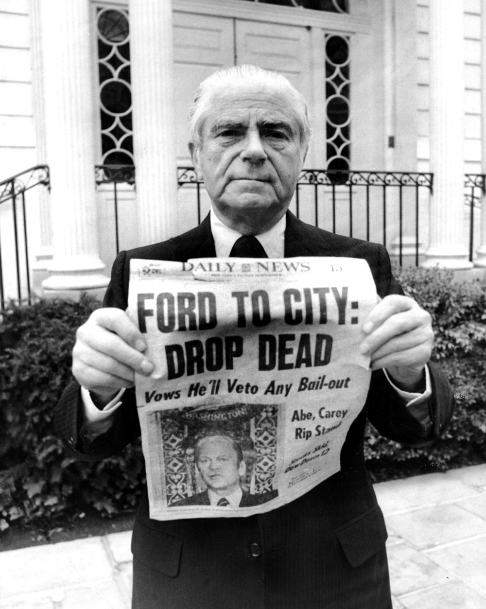 """In 1975, New York City was at the brink of financial collapse. President Gerald Ford gave a speech saying that he would oppose any federal assistance to help save the City. """"Ford to City: Drop Dead"""" was the famous headline that ran on October 30th, 1975 in the New York Daily News, as shown here held by Abraham Beame, Mayor of New York City from 1974-1977. Credit: Getty Images"""