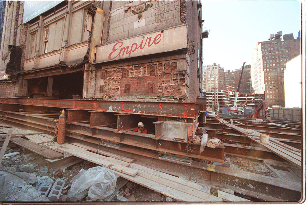 Construction workers putting the Empire Theatre on lifts for its move west. Credit: The New York Times