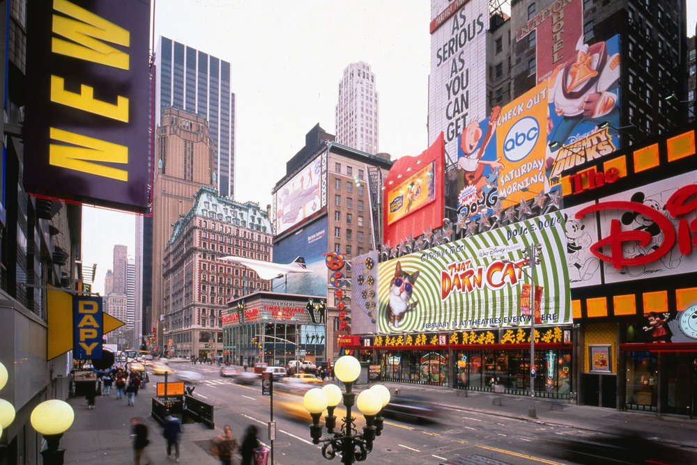 View of 42nd Street looking East in the early 1990s. Before the office towers went up, the street was lined with gig, bright, bold signage, recalling the block's history, and drawing visitors back to the street.. Credit: Peter Aaron/Otto for Robert A.M. Stern Architects