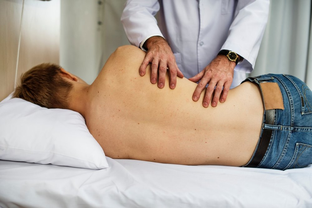 doctor examining patient back.jpg