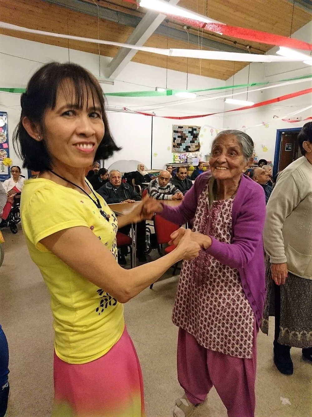 Noo (staff) and Service user dancing (left to right)