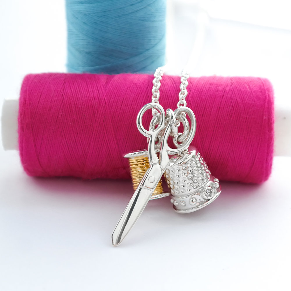 Silver sewing charm necklace with thimble scissors and cotton
