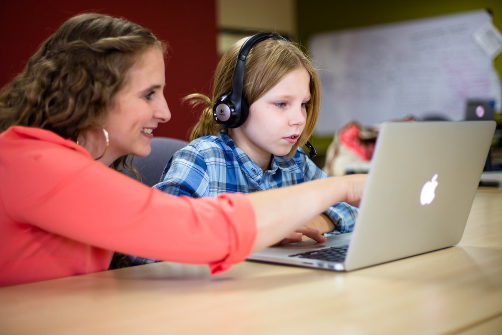 teacher helping student wearing headphones on computer