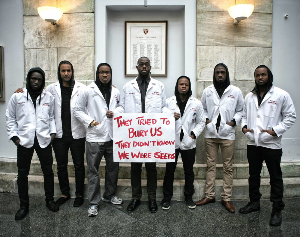 "Picture courtesy of  Chidi Akusobi  (far left). In this powerful photo from 2014, Chidi and a group of his classmates from Harvard Medical School show their solidarity with the Black Lives Matter movement while carrying an English translation of the famous Mexican proverb "" Quisieron enterrarnos, pero se les olvido que somos semillas."""