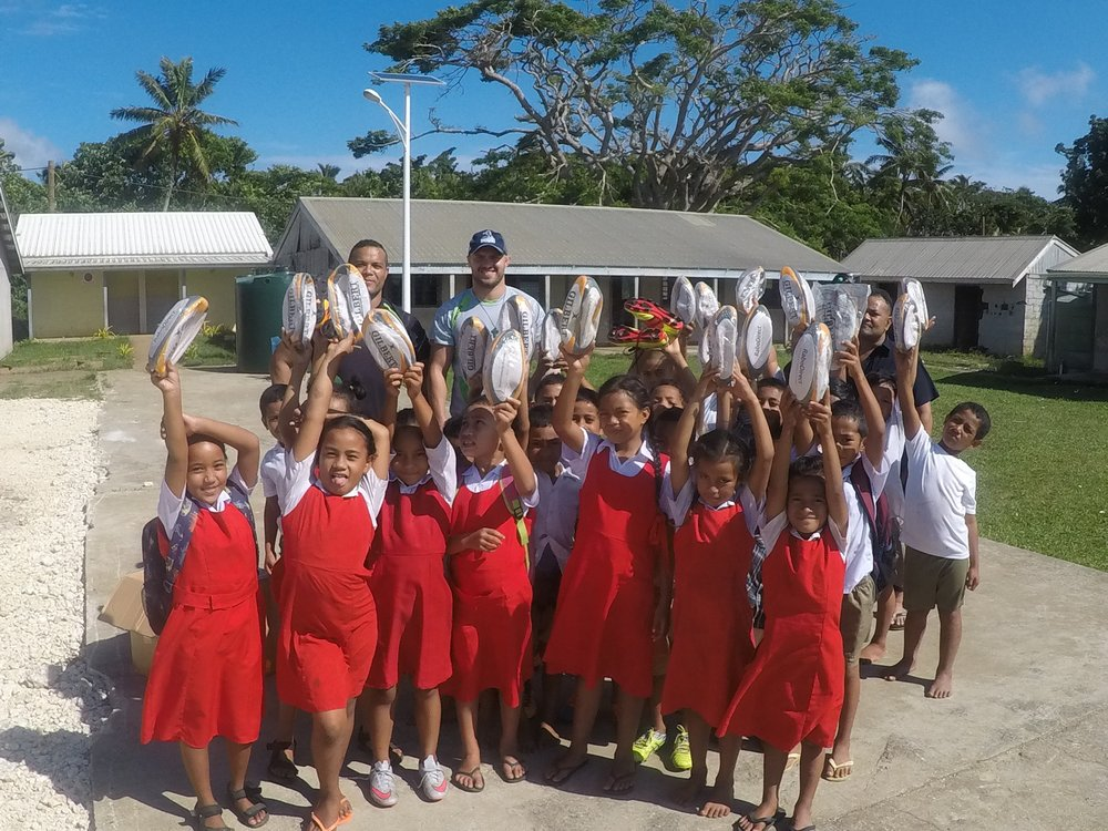 Handing out rugby balls to young girls and boys at a local school - lots of smiles!