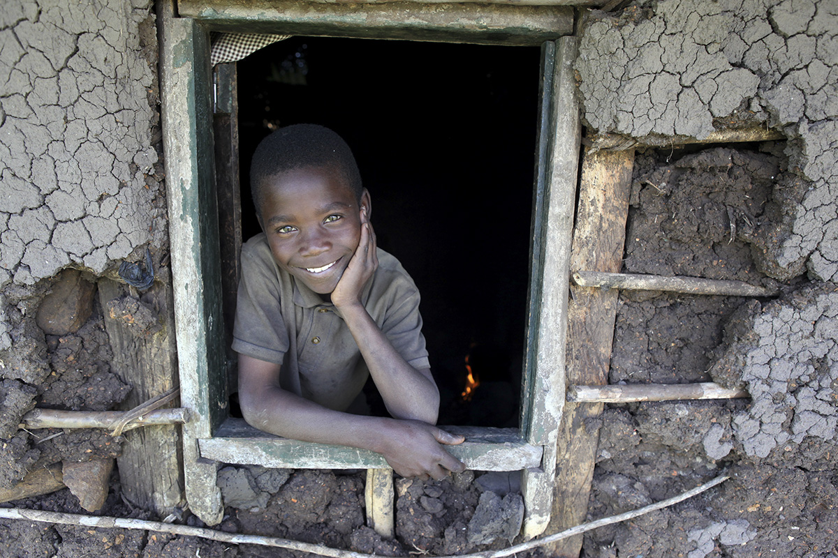 Victor Owino, 9, stares out the window of the home he shares with his four older brothers in Homa Bay, Kenya. Photographing at either eye level or slightly below gives a sense that the person in an image is someone to look up to and admire. Photo courtesy of Sara A. Fajardo/Catholic Relief Services