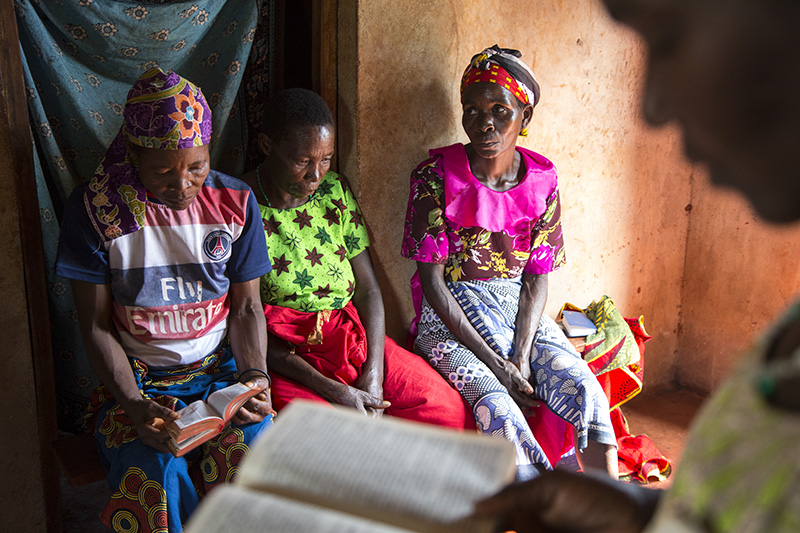 Berta Mapunda, back from left, Cosma Komba, and Wilfirda Ngonyani, listen as their friend Gertruda Domayo reads from her bible in Nakahegwa, Tanzania. Using a wide-angle lens to get closer helps an audience enter a story and feel more connected to the people in an image. Photo Courtesy of Sara A. Fajardo/Catholic Relief Services