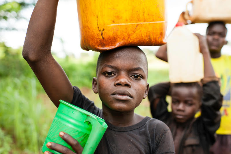 Donatien Voungoukpala, 13, with his brothers Fleuri Rodrigue Hipai, 17, and Aime Bera-Mbolikia, 10, go to fetch water at a a nearby spring, their principle water source. Rounga Village, Bangassou, Central African Republic. Photo by Sean Sheridan for Mercy Corps