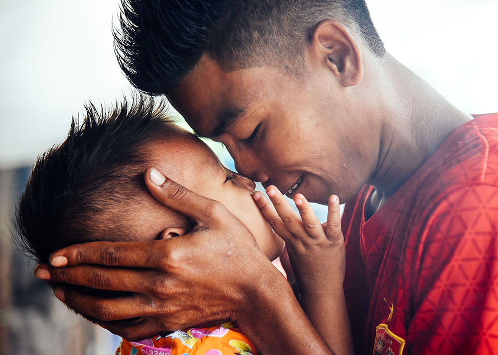 A father and son have a moment in Twantay, Myanmar during a visit to the Delta Region with Proximity Designs. Photo © James Roh.