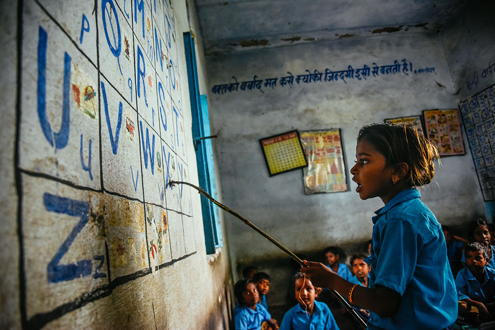 A young girl practices the english alphabet in front of her class during school in Rajasthan, India. Educate Girls, a local nonprofit, focuses on encouraging young girls to attend school in order to improve their opportunities in life. Photo © James Roh.