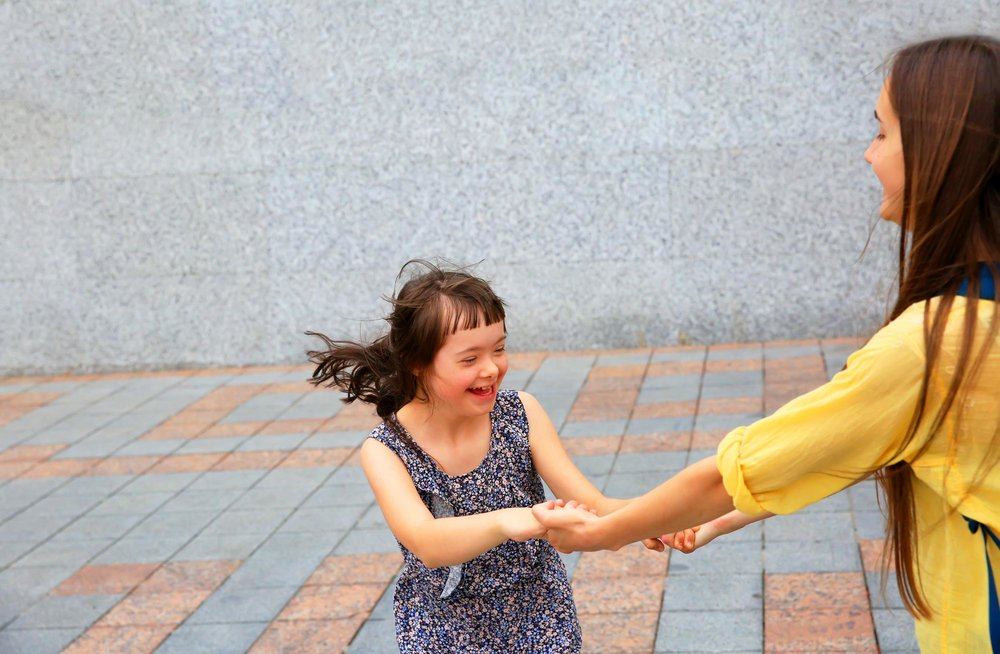 Girl with Down Syndrome Dancing and Holding Hands with Woman in Yellow Shirt