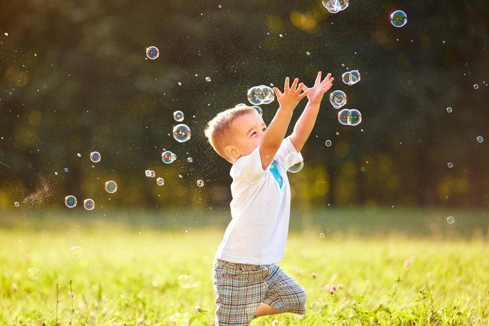 Boy Chasing Bubbles in Field of Green Grass.jpg