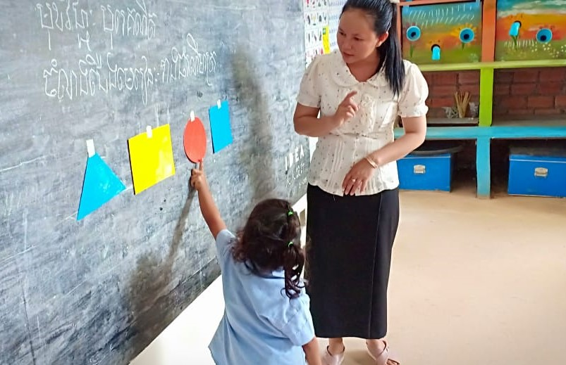 Photo: Tamom Village Based Preschool Teacher Kong Channy shows student the different forms of geometry.