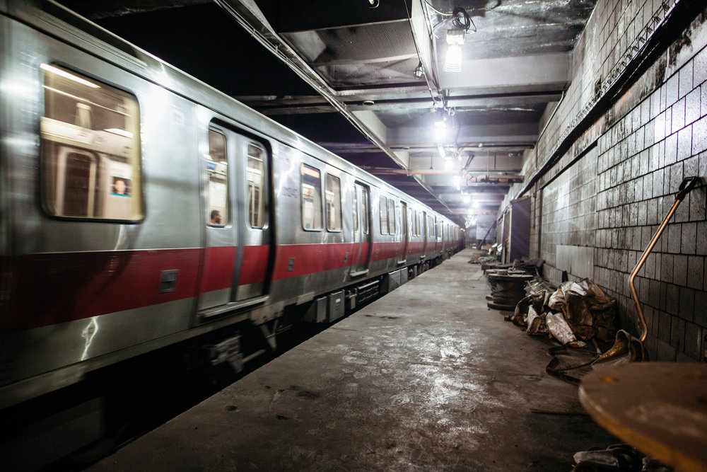 The red line train passing through an abandoned Harvard station.