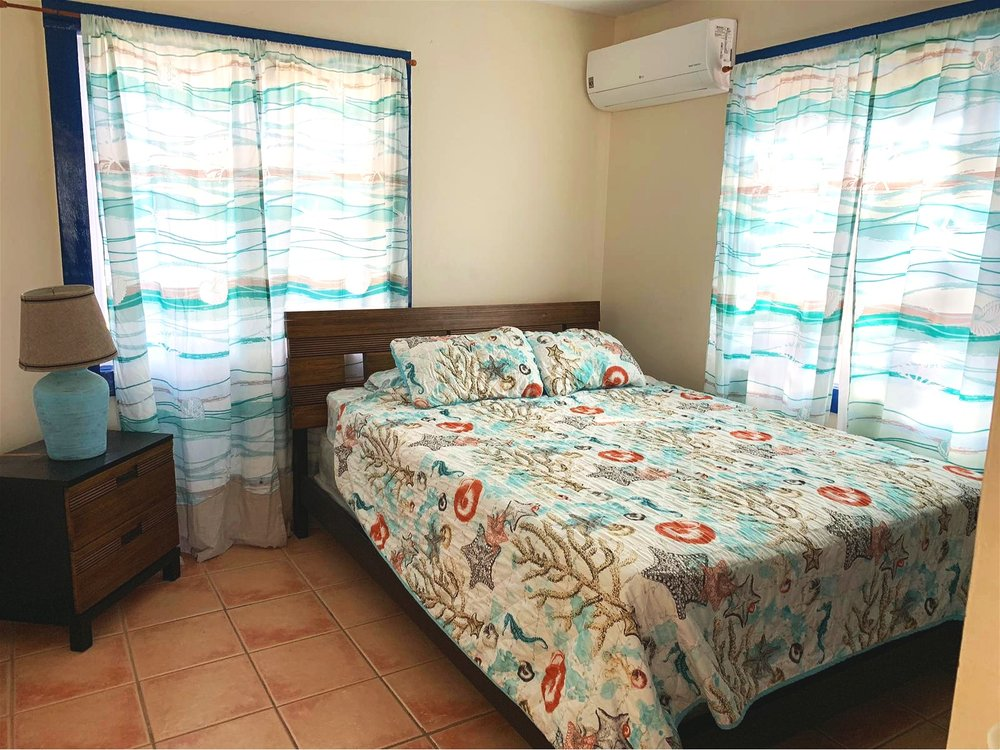 Sleeps 4 - High Season $115-$135 per nightLow Season $100 -$115 per nightTwo Bedrooms w/ Queen BedsWhisper Quiet Console A/C in Each RoomHDTV with Satellite ChannelsLiving Room with Pallet Day BedWIFIFull KitchenHair DryerBalcony with Ocean View