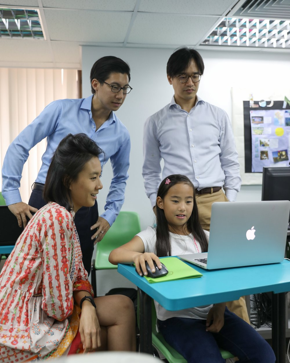 Natalie Chan, Founder of OWN Academy, Douglas Wu, Executive Director of Fairland Holdings and Eugene Wong, Director of Posang Capital with student Evelyn Kwok discussing her design for an inclusive rainbow staircase