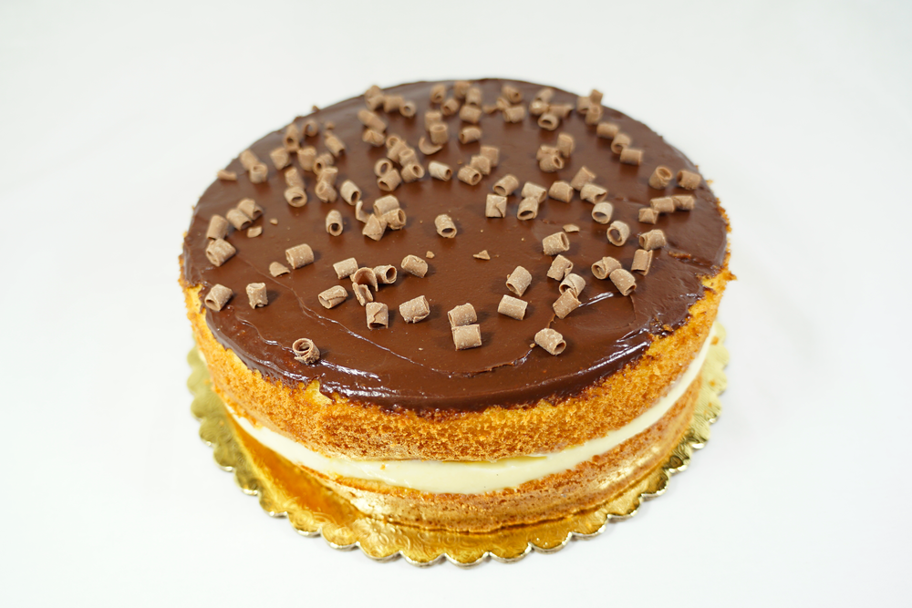 Boston Cream - 2 layers of genoise sponge cake misted with orange syrup, layer of apricot jam and bavarian cream filling. Topped with ganache and covered with chocolate shavings.