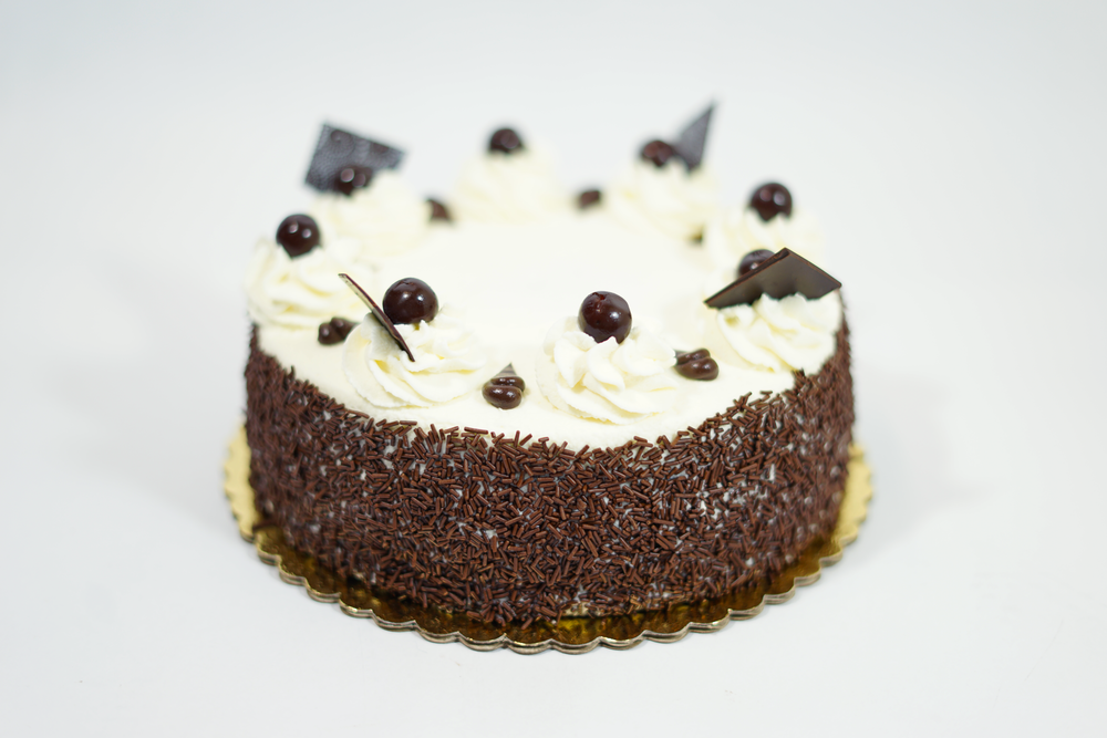 Black Forest - A chocolate cake with cherry liquor syrup and homemade cherry filling. Iced with whipped cream and decorated with chocolate curls on the sides.