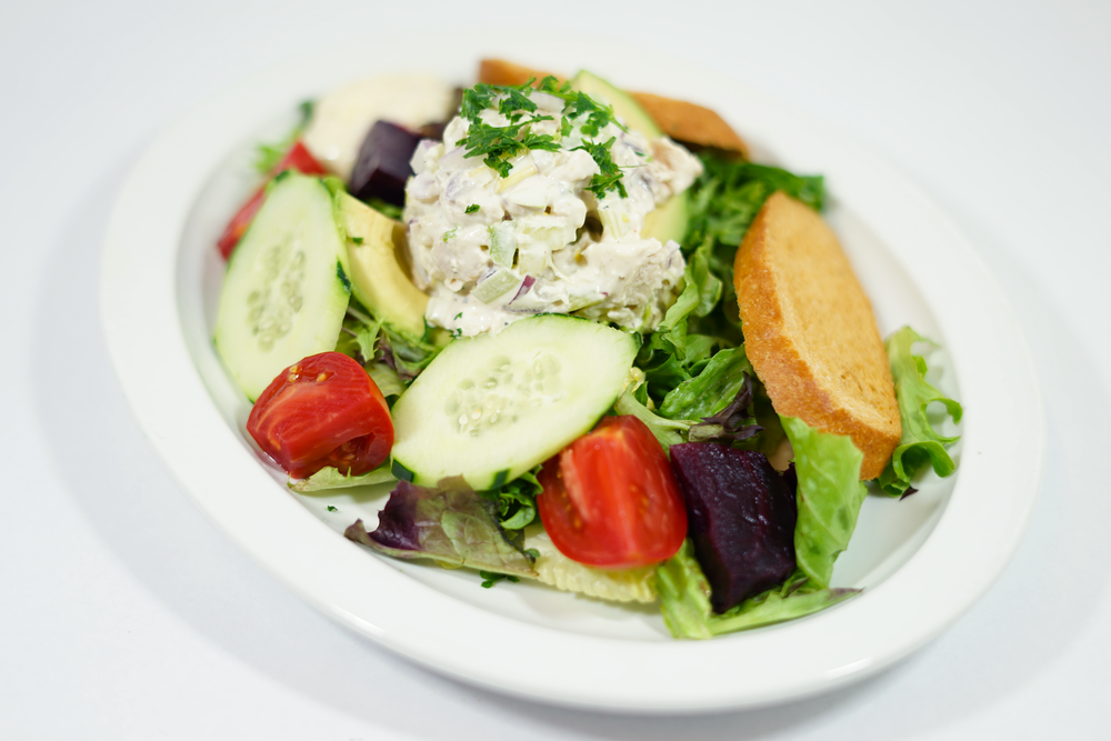 Avocado Chicken - Dijon vinaigrette mixed with a bed of romaine lettuce and spring mix greens, half of an avocado, aioli, seasonal vegetables and a scoop of chicken salad. Garnished with seasonal vegetables and sliced bread toast.