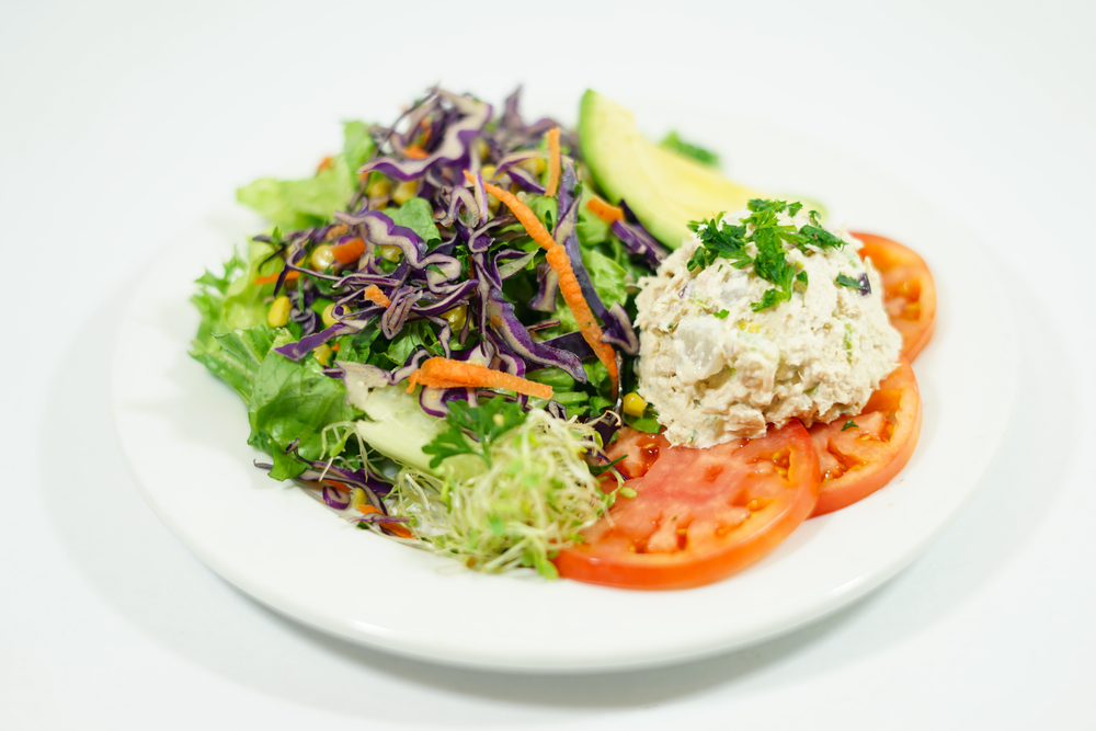 Country Salad - A bed of spring mix and romaine lettuce, topped with shredded mix of cabbage, carrots, corn and parsaley, sliced tomatoes, sprouts, avocado slices, and your choice of scoop of tuna or chicken salad.