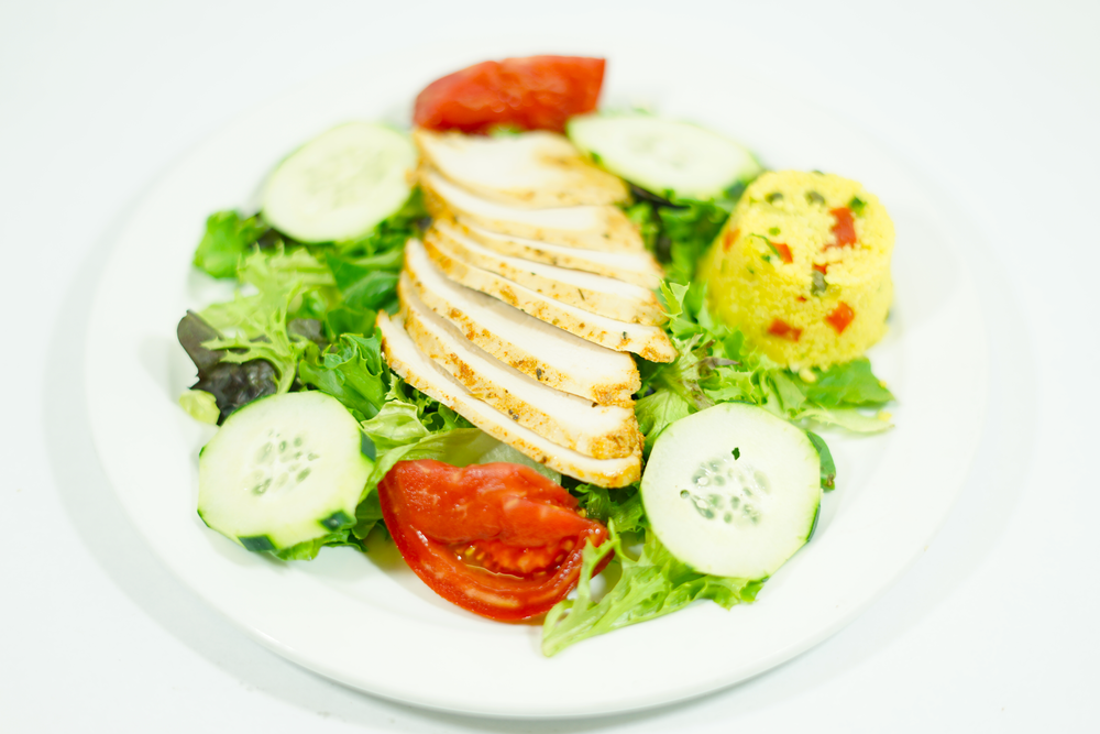 Mediterranean Chicken - A bed of mixed greens with cold chicken breast, couscous; garnished with cucumbers, tomato wedges and Balsamic dressing on the side.
