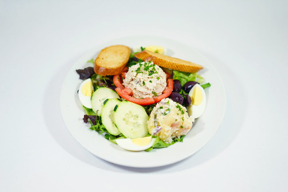 Nicoise - On a tomato crown with your choice of Chicken or Tuna salad served with homemade potato salad, kalamata olives, hard boiled eggs on a bed of mixed greens tossed in Dijon vinaigrette. Garnished with sliced bread toast.