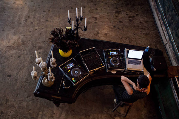 A DJ preparing at a rounded booth is seen from above at a SecretEATS event.