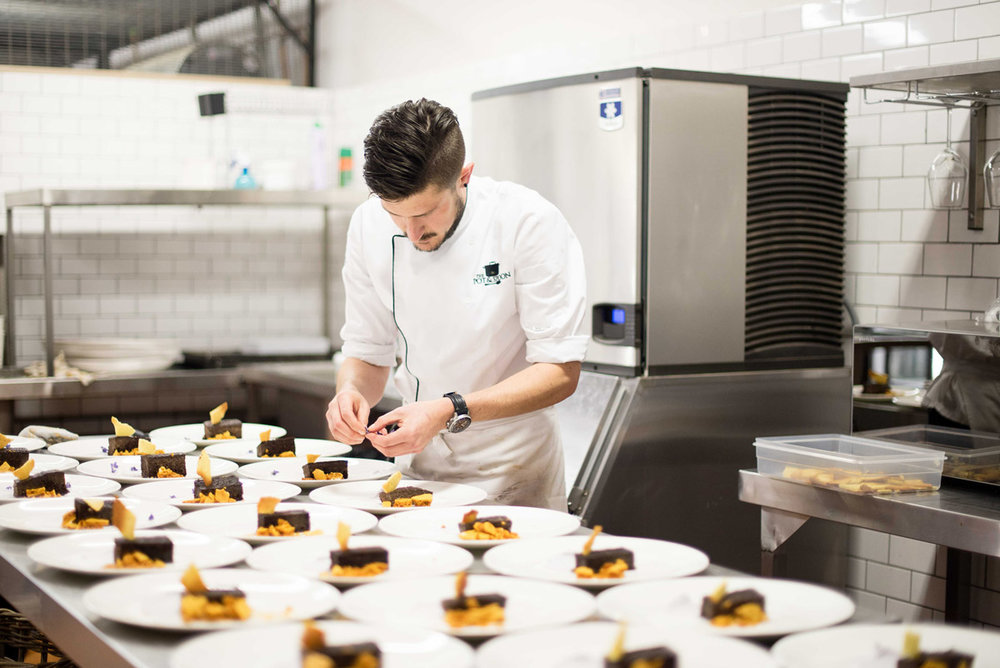 Rows of chocolate-topped desserts are hand-finished by a SecretEATS private event chef.