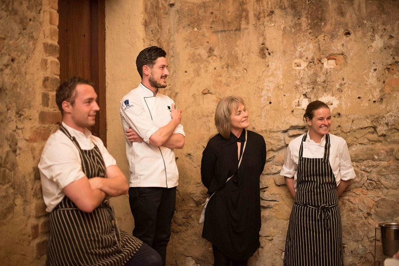 Three chefs and a SecretEATS venue host lean against a wall, smiling and watching guests out of frame.