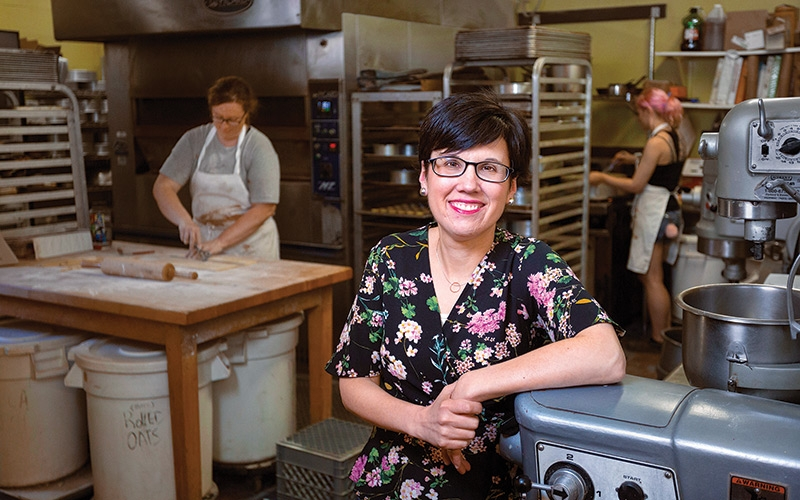 Stacy Begin, owner of Two Fat Cats… - in the kitchen at the India Street location. In 2012, Begin and her husband, Matthew Holbrook, bought the bakery from its original owners. Since then, revenue has doubled and the couple opened a second location in South Portland.