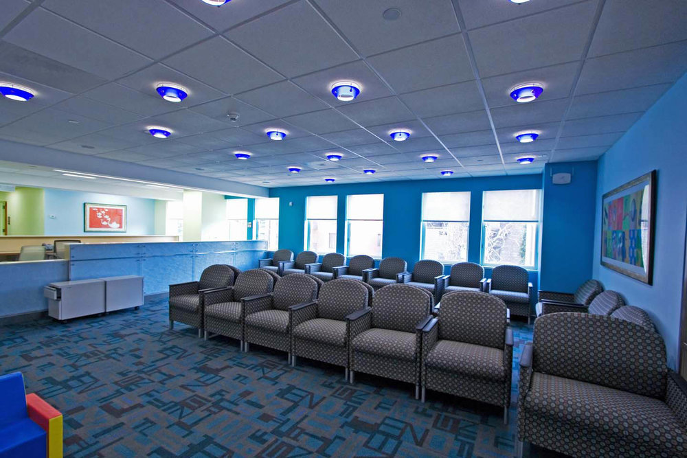 """Color, color was our primary tool in this pediatrics waiting room. The use of blue was meant to grab the positive attention of the children while also creating an over all calming space. The several blue shades found in the alphabet carpet, the glass housing around the down-lights and the reflective patterned surface of the reception desk fostered a """"blue"""" space that felt more like a playroom rather than an waiting room."""