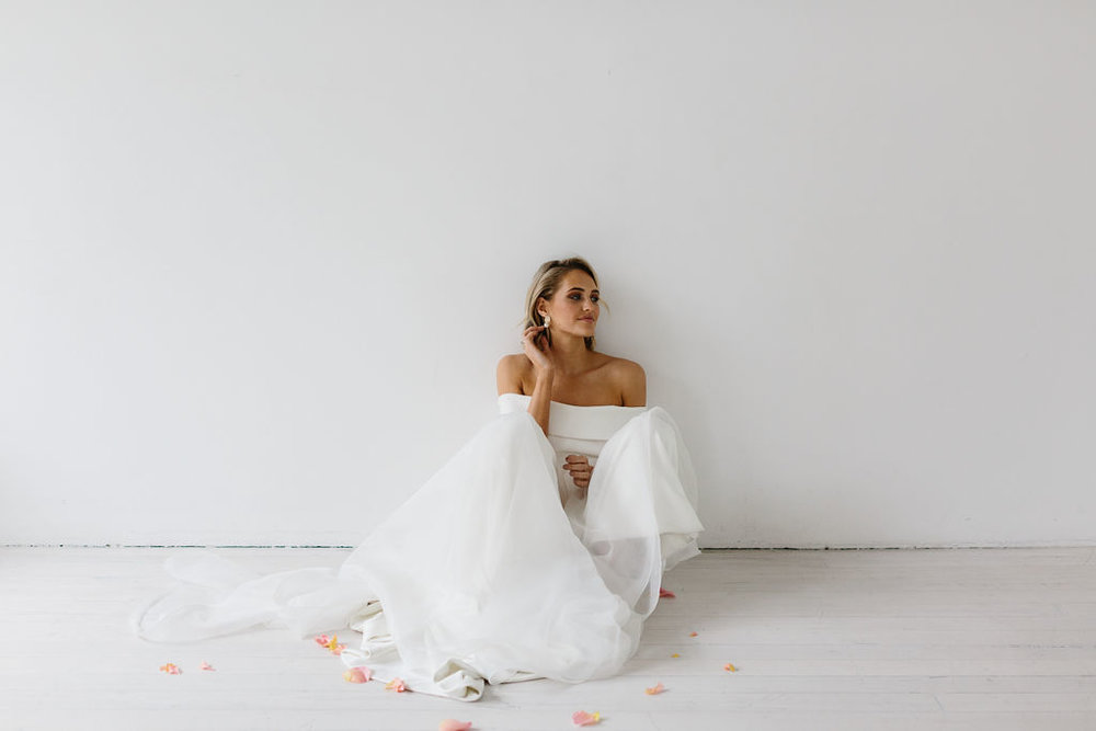 Amelie George Bride in strapless wedding dress sitting on White floor on White wall with rose petals in natural light