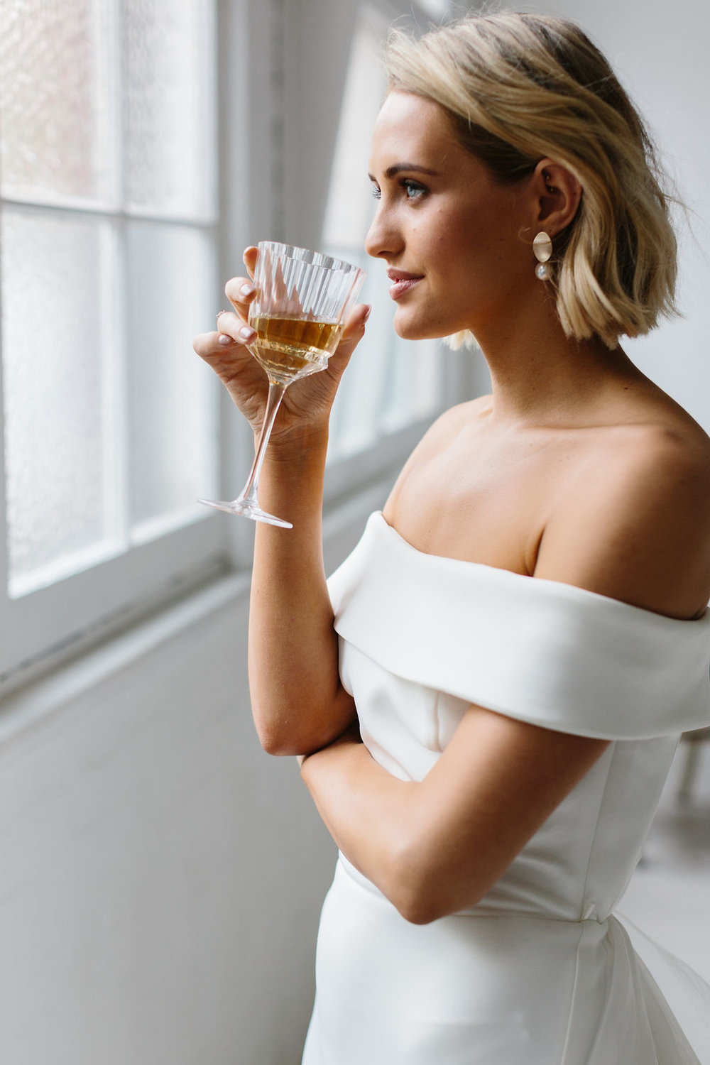 BRIDE GETTING READY DRINKING CHAMPAGNE LOOKING OUT WINDOW IN GOLD PEARL WEDDING EARRINGS AND SHORT BLONDE BRIDAL MESSY UPDO FOR AMELIE GEORGE CAMPAIGN
