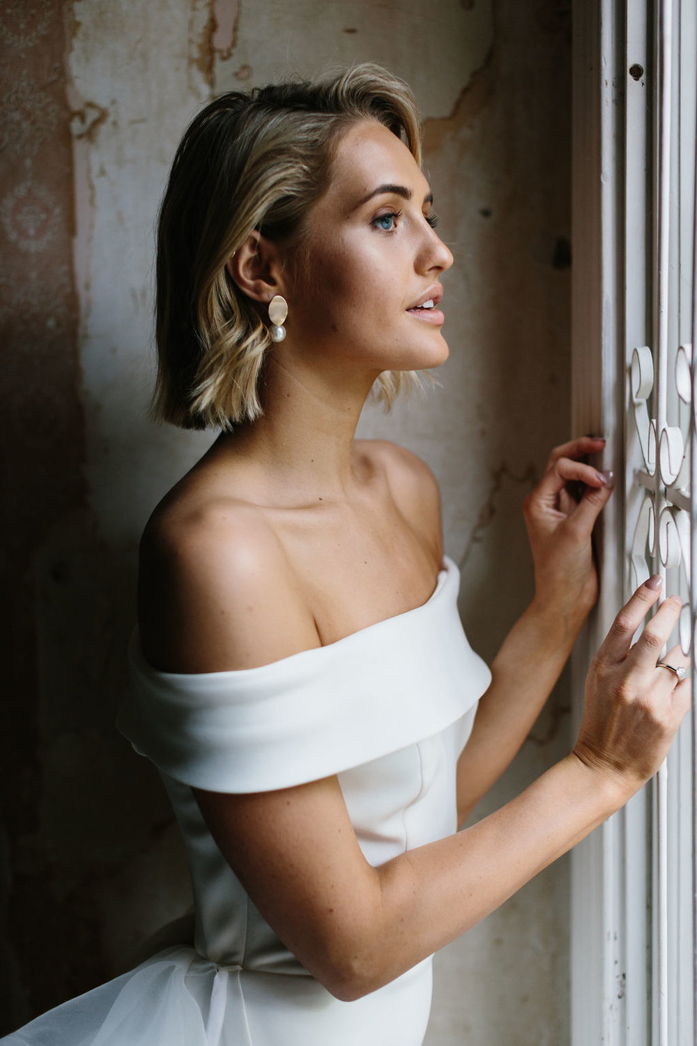 Perfect Bridal highlight makeup with bronze lowlight and pearl gold wedding earrings for Amelie George Campaign in vintage ballroom looking out window wearing offshoulder wedding dress