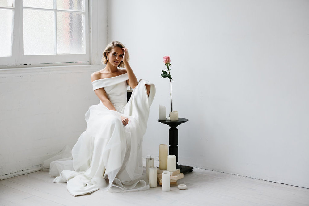 AMELIE GEORGE CAMPAIGN NATURAL MODERN BRIDE IN OFFSHOULDER DRESS ON CHAIR WITH CANDLES AND SINGLE ROSE BOUQUET