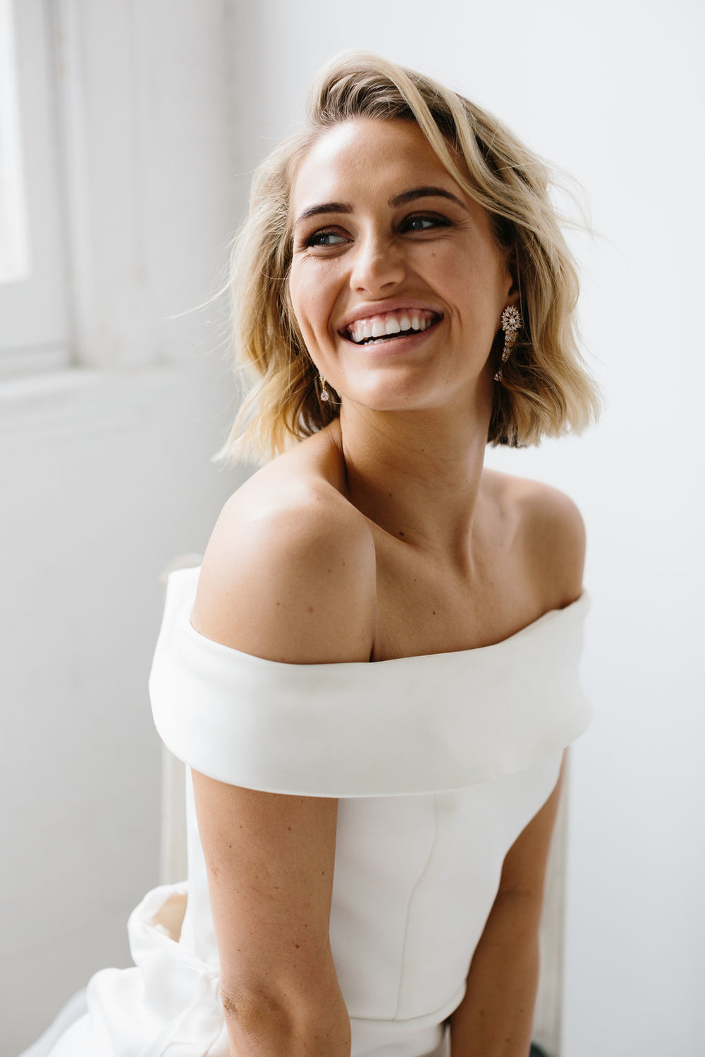 Stunning smiling natural modern bride with hair out and chandelier earrings in wedding photo wearing offshoulder wedding dress for Amelie George Jewellery Campaign
