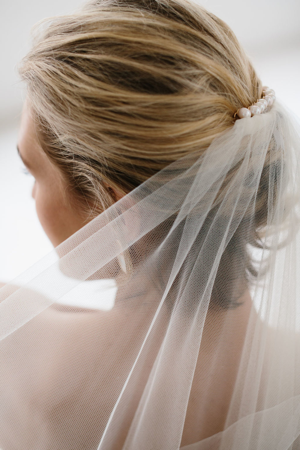 Natural messy bridal updo with pearl hair pins in veil for Amelie George Jewellery Campaign
