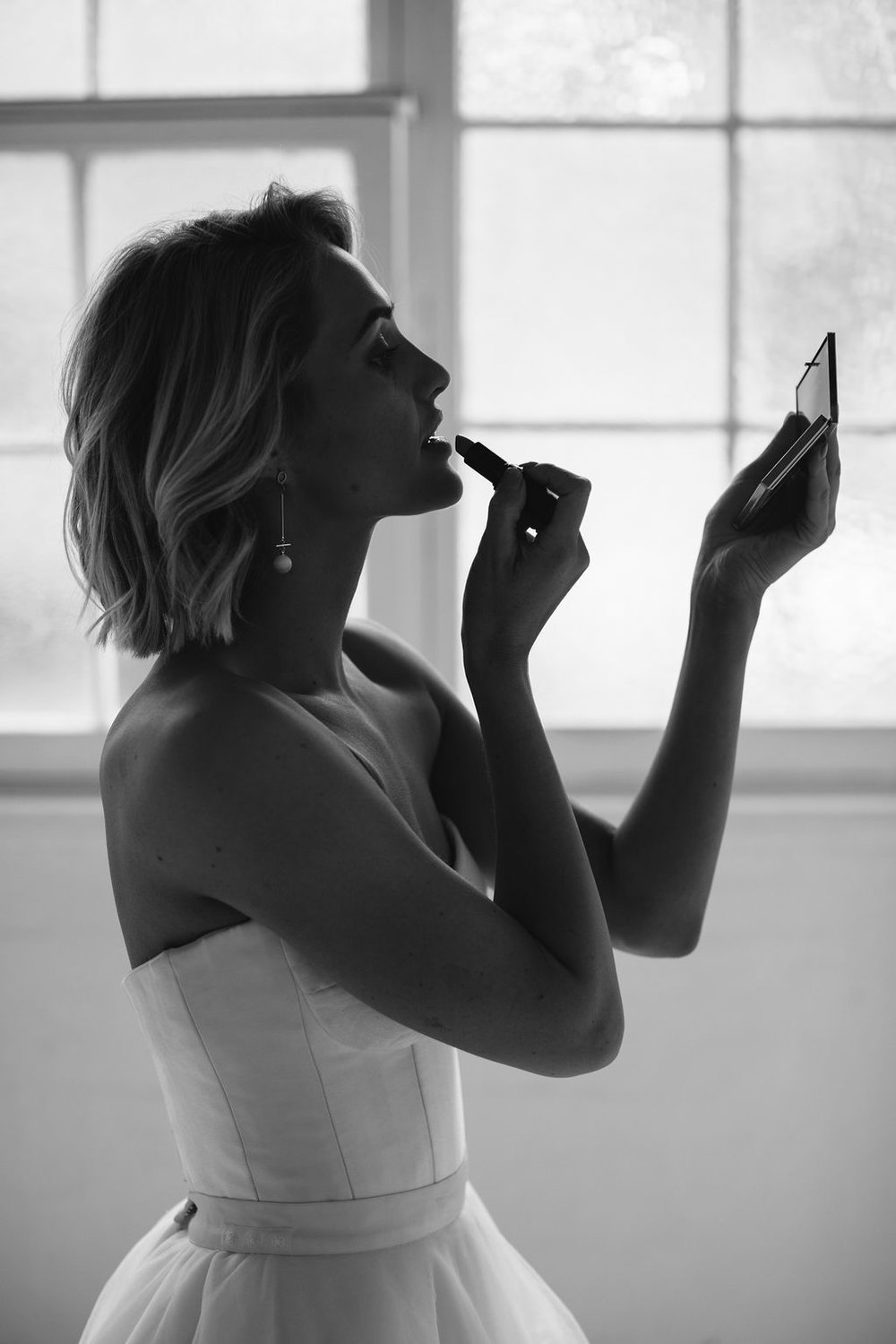 Bride getting ready putting on lipstick in mirror in black and white only wearing long gold cross pearl modern wedding earrings and blonde wavy short hair in strapless dress for Amelelie George Campaign