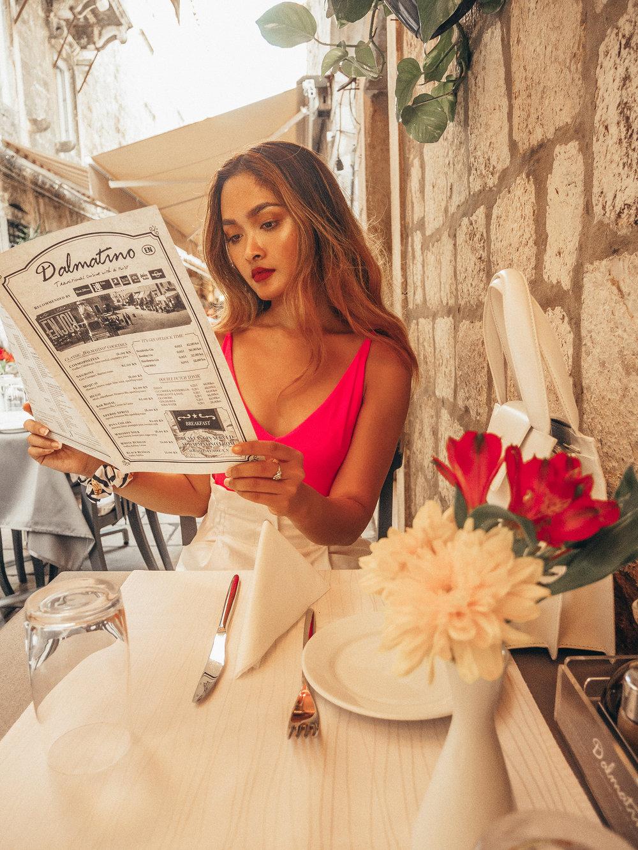 Cindy reading the menu at Konoba Dalmatino