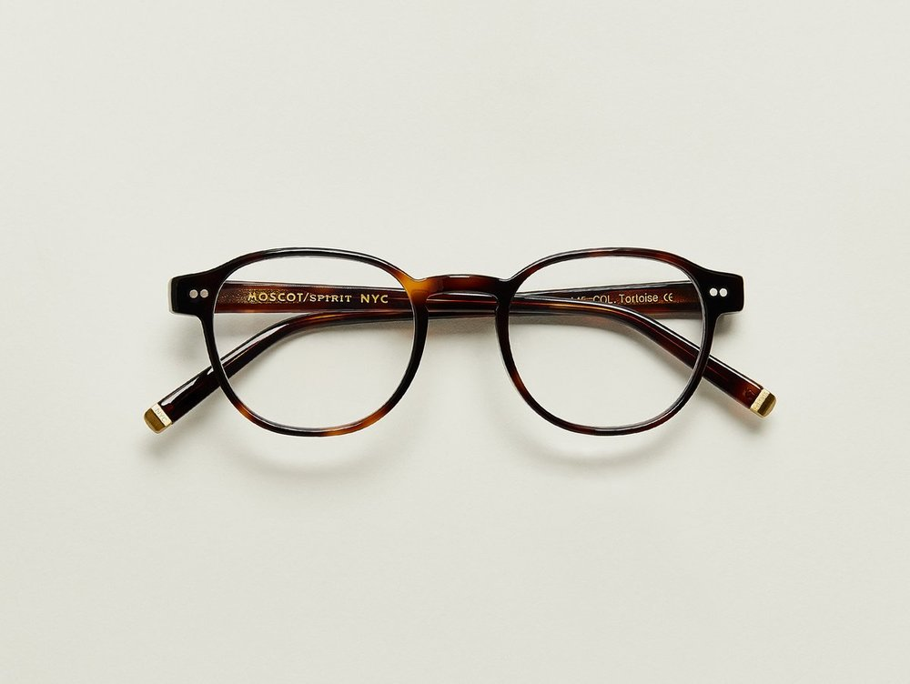 MOSCOT - Arthur Opticals   £245   COLOUR  Tortoise   SIZE  50  This frame is based on The LEMTOSH silhouette, but with a slimmed down look, a thinner gauge, and a key hole bridge that's just a bit more business. They say not to mix business with pleasure, but we couldn't help ourselves.  Features two dot rivets  Comfortable key hole nose bridge  Includes acetate nose pads  3-Barrel hinge  MOSCOT temple engravings