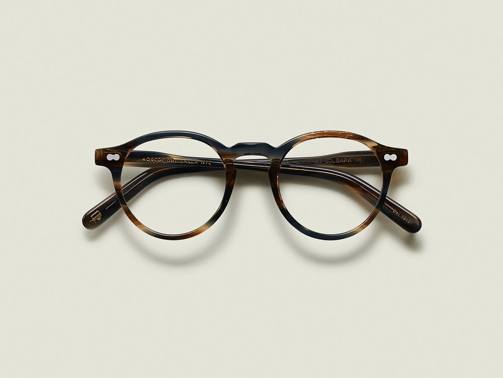 MOSCOT - Militzen Opticals    £245    COLOUR  Bark   SIZE  46  The round, full-vue MILTZEN, first introduced in the 1930s, is eponymously named for our Uncle Heshy, who inexplicably everyone called Uncle Miltzen. And it stuck. So there you go, world... The MILTZEN.  Handcrafted using Italian acetate  Features adjoined dot rivets  Comfortable key hole nose bridge  Includes acetate nose pads  3-Barrel hinge  MOSCOT temple engravings